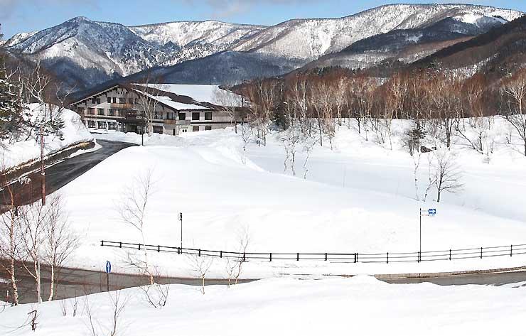 雪に覆われた旧蓮池ホテル跡地(道路に面した中央部分)。蓮池(右)に面し、山の駅(奥)もほど近い