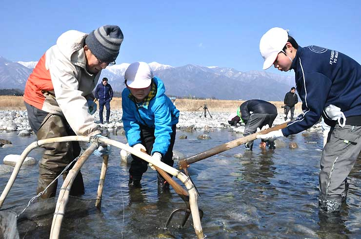 菅沼さん(左)に教わり、ざざ虫漁を体験する子どもたち