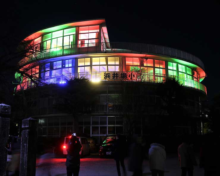ライトアップされ、闇夜に浮かび上がる飯田市浜井場小学校の「円筒校舎」=27日午後6時32分
