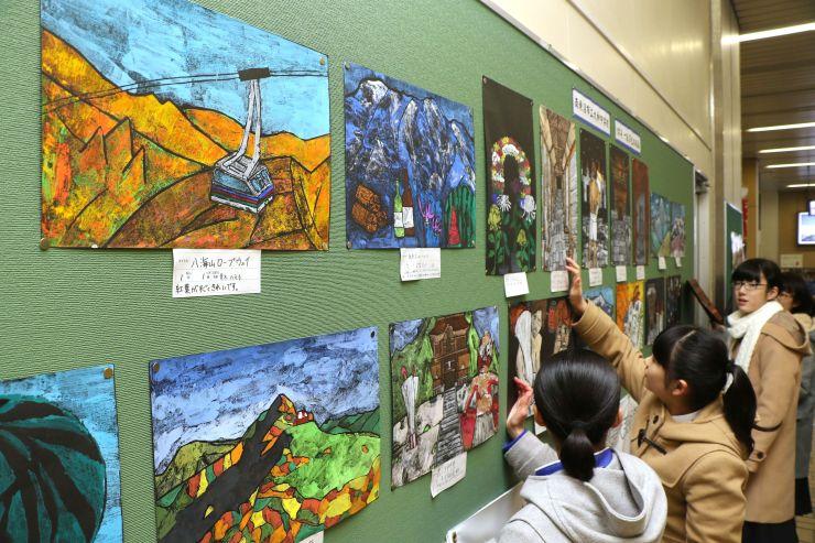 浦佐駅構内に木版画を飾る大和中の生徒ら=南魚沼市