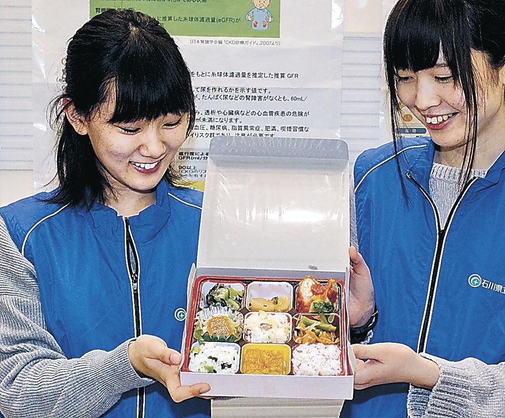 レシピを考えた「愛彩弁当」を披露する学生=かほく市のイオンモールかほく
