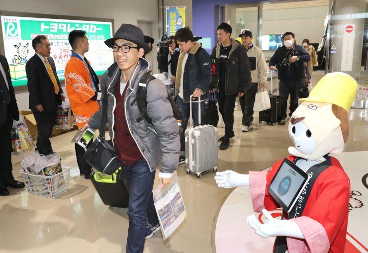 大阪からの初便で新潟に到着した乗客たち。新潟県観光関係者らが出迎えた=3月1日、新潟空港