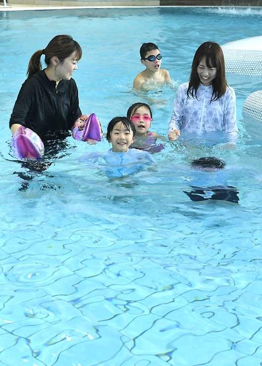 早速プールに入り、笑顔を見せながら泳ぐ子どもら=1日、長野市のサンマリーンながの