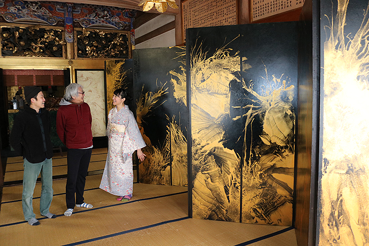 金色の波紋のような模様が特徴の「波動」を前に話す(左から)公文名さん、山村さん、ゐくみみさん