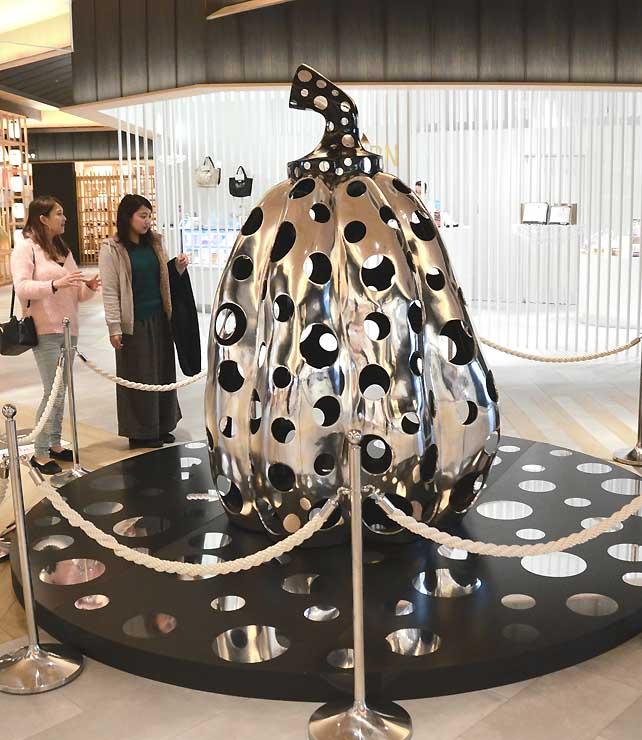 イオンモール松本の「空庭」に一足先に置かれた作品「宇宙にとどけ、水玉かぼちゃ」。通り掛かった人たちが驚いた様子で見ていた
