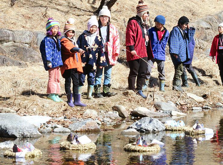 さんだわらに載せて川に流したひな人形を見送る北相木小の児童ら