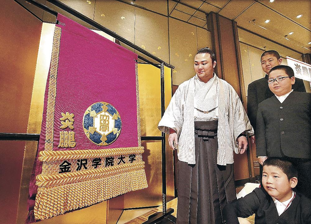 披露された金沢学院大の校章、校名入りの化粧まわしと炎鵬=金沢市内のホテル