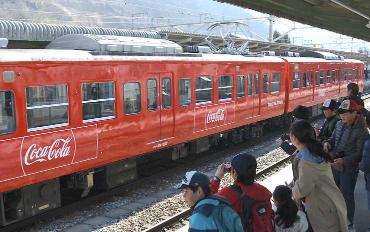 鉄道ファンに見守られながら運行を始めた「コカ・コーララッピング電車」=4日、千曲市のしなの鉄道戸倉駅