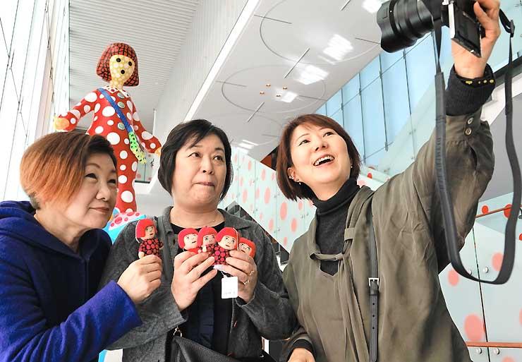 購入したマスコット人形を手に、巨大な人形「ヤヨイちゃん」の前で記念撮影する草間ファンの女性たち=3日午前11時