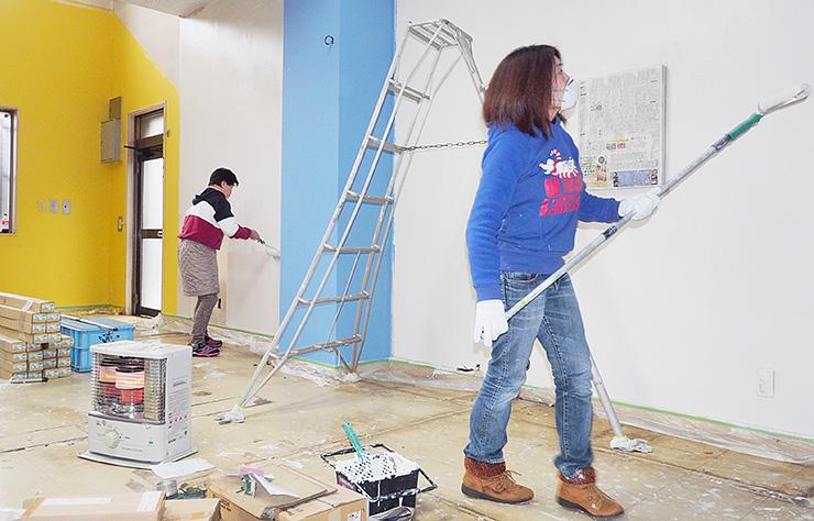 旧新湊信金新町支店の内部の壁を塗り替える関係者=射水市中央町
