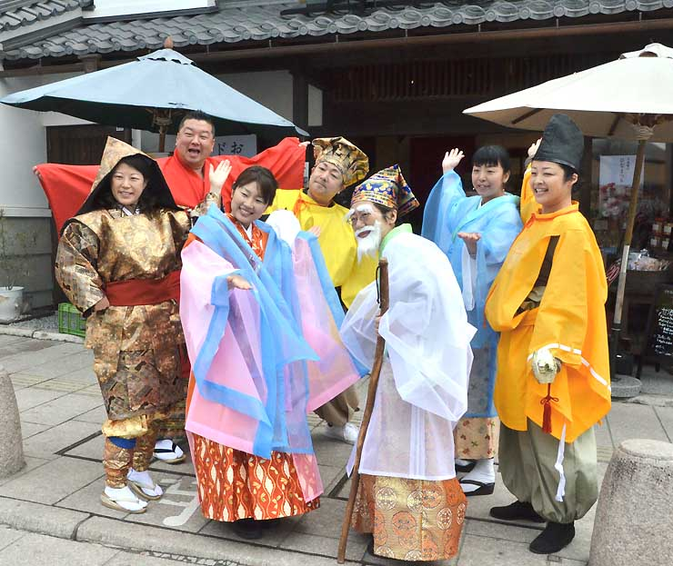 善光寺に続く中央通りでの撮影で、「七福神」になりきってポーズを取る吉沢さん(左から3人目)ら「善光寺界隈作業部会」のメンバー