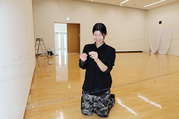 漆を塗った絹糸を張った空間造形作品を仕上げる森田さん=アートハウスおやべ