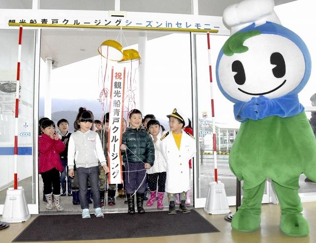 くす玉を割り観光船の今季運航開始を祝う園児たち=9日、おおい町成海の「うみんぴあ大飯」