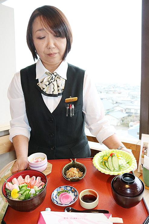 「新湊紅白丼定食」を持つ第一イン新湊の南部好美料飲支配人=射水市善光寺