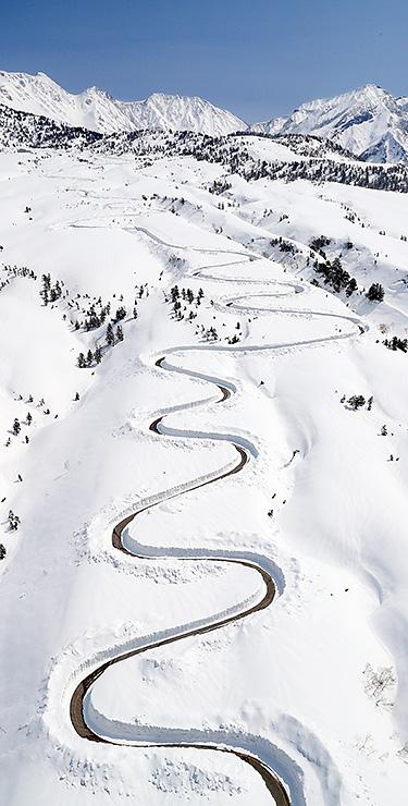 除雪され雪原に曲線を描く七曲付近の高原バス道路=13日午前11時35分ごろ、本社チャーターへりから