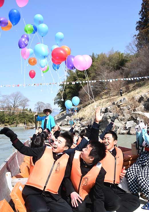 川開きを祝い、舟の上から色とりどりの風船を飛ばす泰阜中の3年生