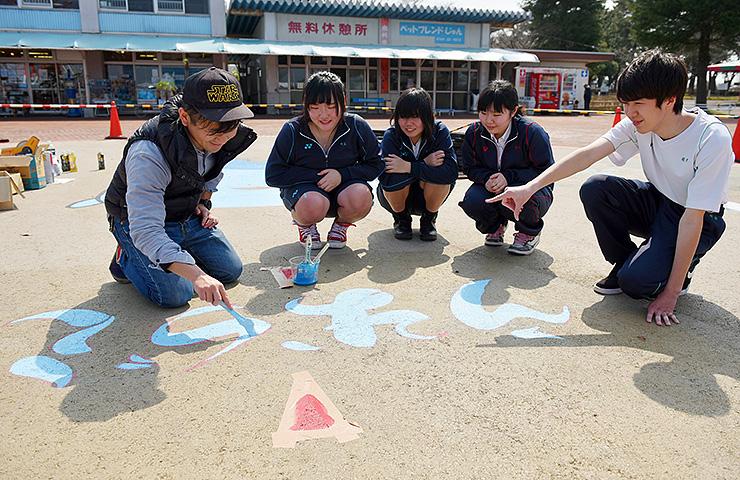 ミラたんの文字に色を塗る野村さん(左)と美術部員=魚津水族館前