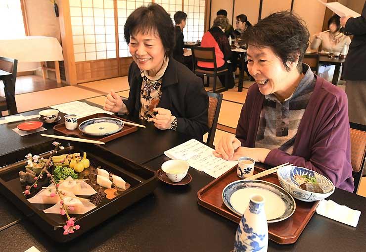 桃の花とともに漆器に盛られた料理を楽しむ来館者=須坂市の田中本家博物館