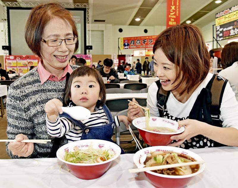 全国から集まった人気店のラーメンを楽しむ来場者=14日、福井市の県産業会館