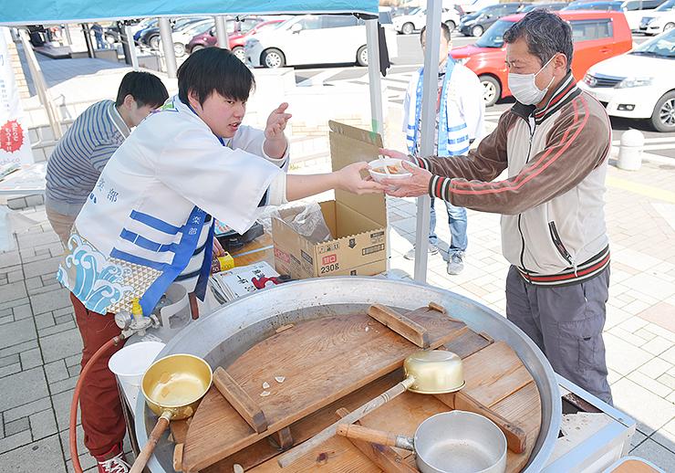 魚津の野菜などが入った鍋料理を販売する学生ら