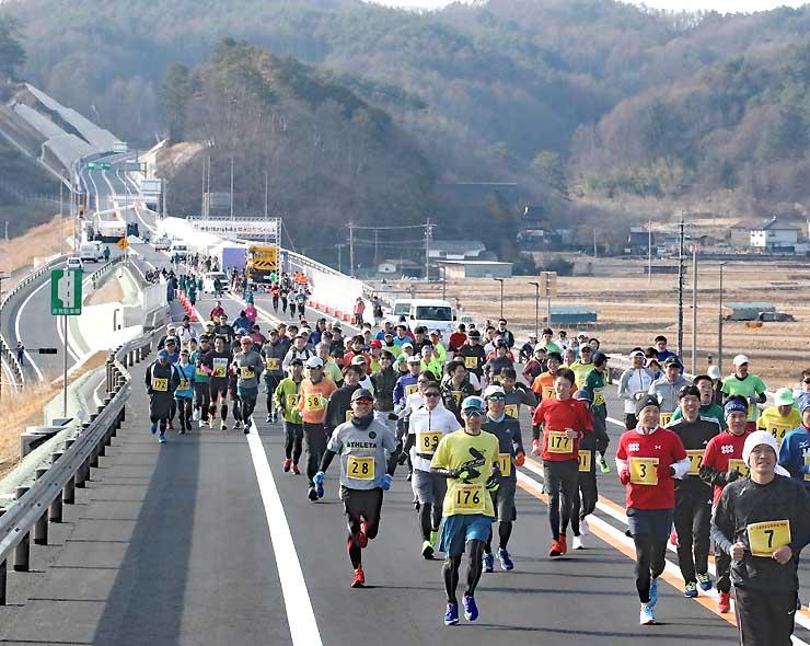 開通前の高速道上を走るランナーたち=18日、中部横断道佐久臼田IC付近
