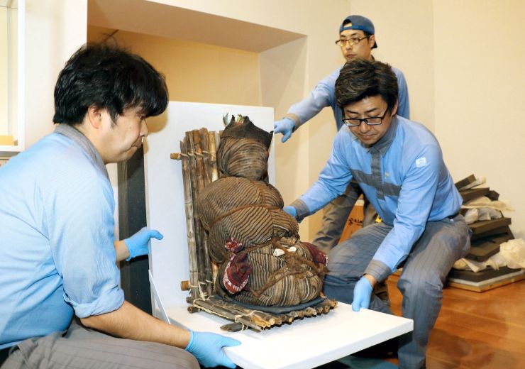 展示されるミイラを慎重に運ぶ作業員=19日、新潟市中央区の県立万代島美術館