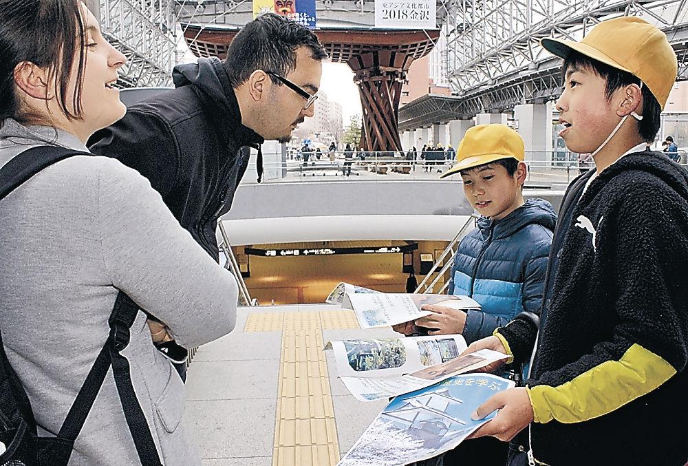 パンフレットを観光客に見せる児童=JR金沢駅前