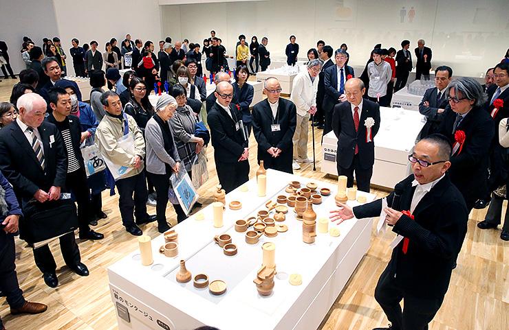 さまざまなパーツを組み合わせて容器を作る体験コーナーを説明する佐藤さん(手前右)=富山県美術館