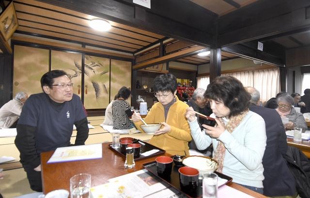 水野さん(左)のおもてなしを受けながら、卵かけご飯を味わう客たち=21日、越前町熊谷の「くまカフェ」