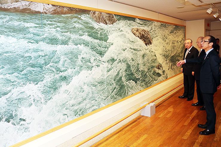 セレネ美術館に移設された絵画「黒部川」を鑑賞する堀内市長(右)ら