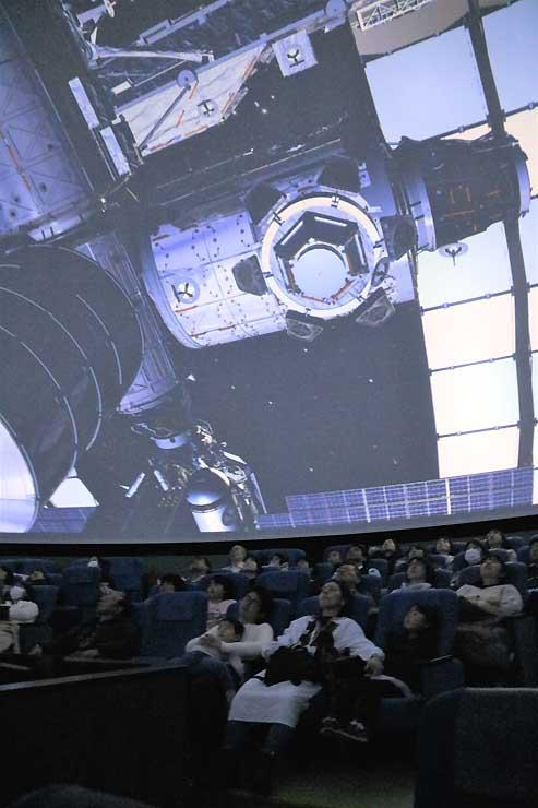 国際宇宙ステーションなどが登場する油井さんの番組を楽しむ来館者ら