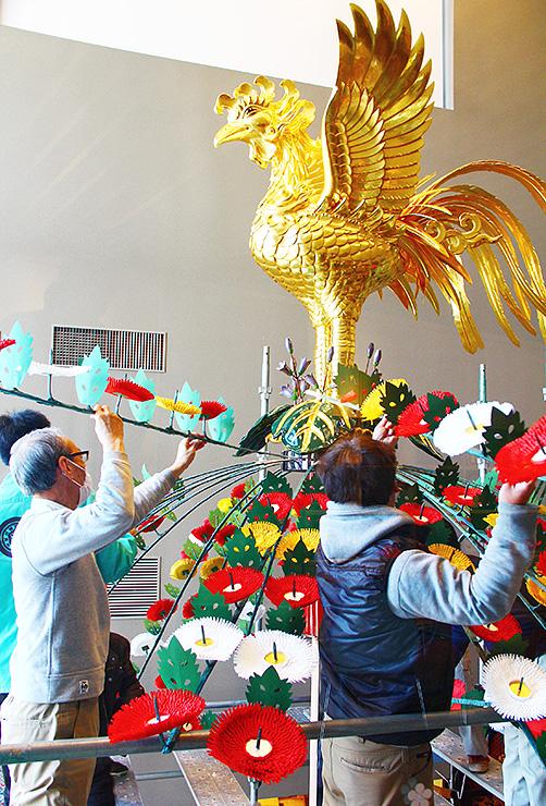 山車の最上部にある鉾留や花傘を取り付ける関係者=高岡市守山町(高岡市提供)