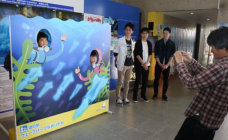 顔出し看板パネルで記念写真を撮る家族。デザインを考えた学生3人(奥)も訪れた