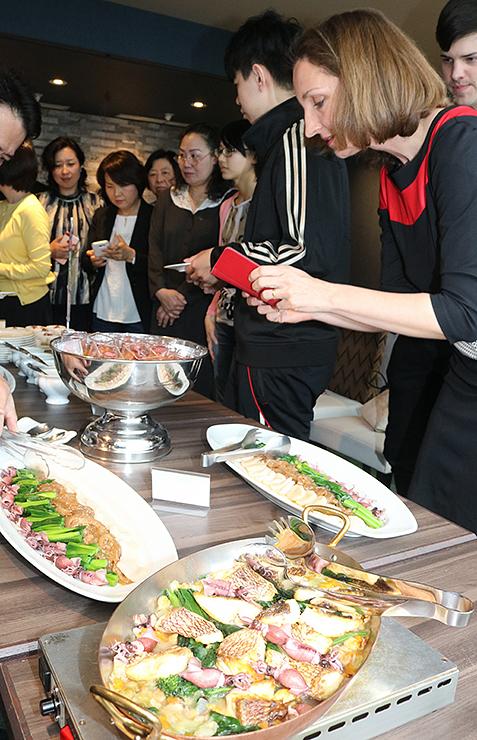 ホタルイカと春野菜を使った料理を楽しむ参加者