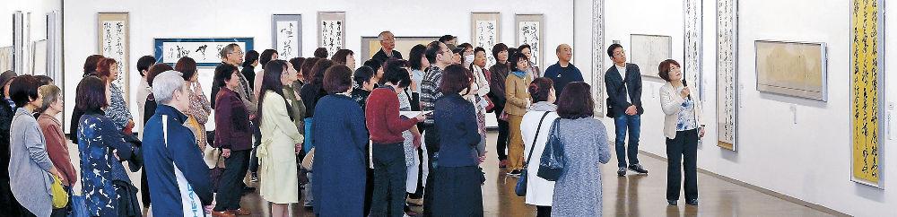 中田さんの解説で書の秀作を鑑賞する来場者=金沢21世紀美術館