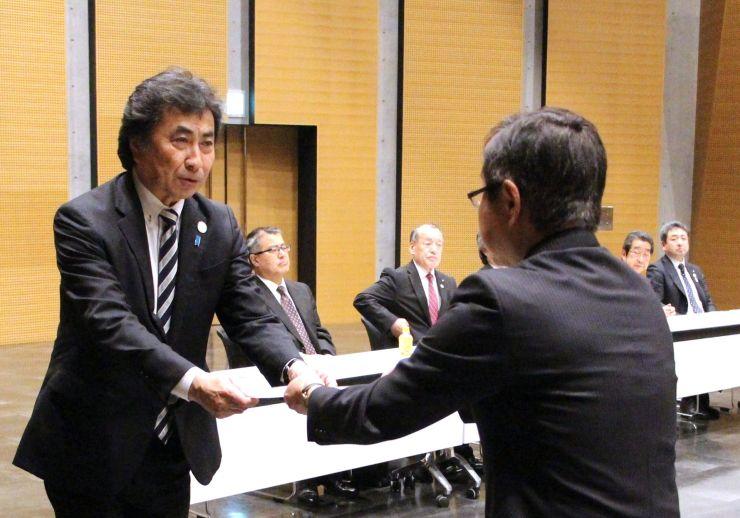 中村充夫観光部長(右)から登録証を受け取る三浦基裕市長=2日、佐渡市両津夷