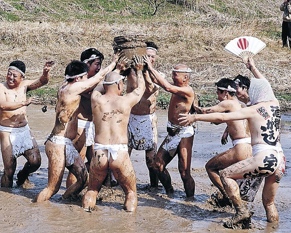 泥まみれになって酒樽を奪い合う男衆=能登町藤波