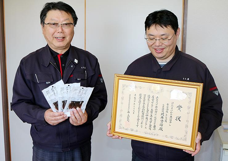 商品と賞状を手に喜ぶ坂井賢治社長(左)と正彦営業部長