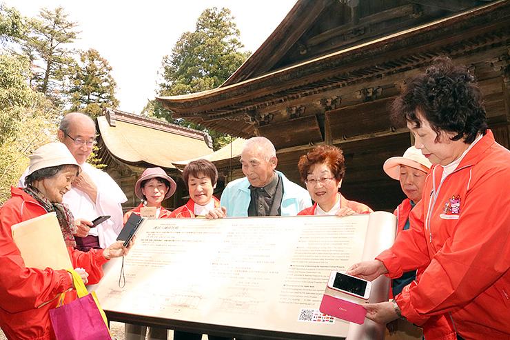 社殿そばの説明板を囲み、埴生宮司(左から2人目)から説明を受けるメルヘンガイドのメンバー