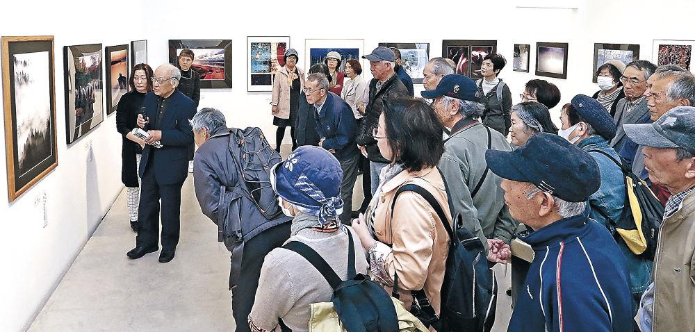 写真の作品解説に聞き入る来場者=金沢21世紀美術館
