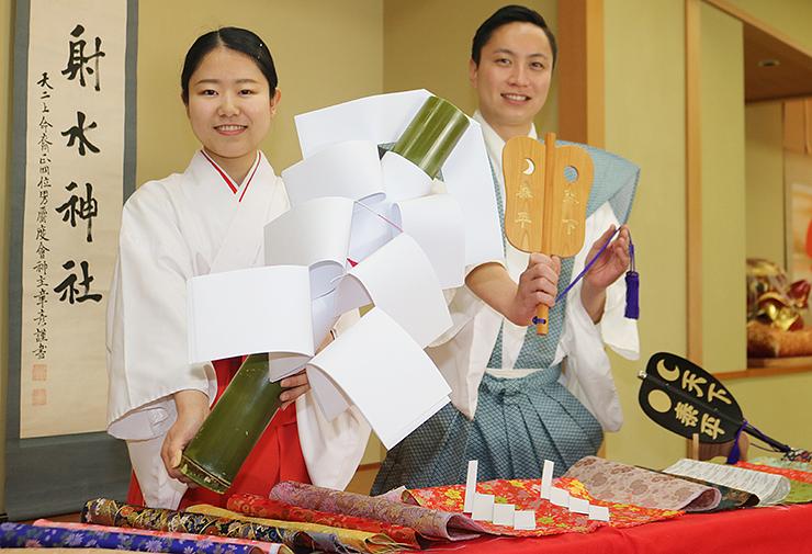 本番で使う軍配と優勝者に贈る八幡幣を手に、イベントをPRする関係者=射水神社