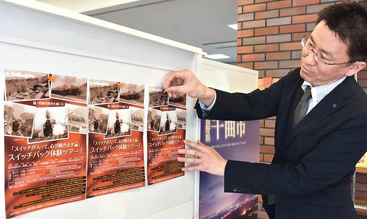 ツアーをPRするため信州千曲観光局でチラシを貼る佐々木さん