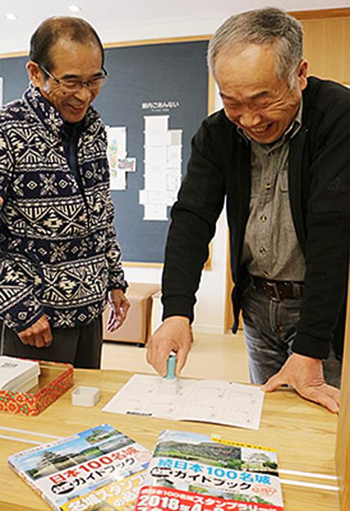 埋蔵文化財センターで、スタンプを押す松田さん(右)=増山城