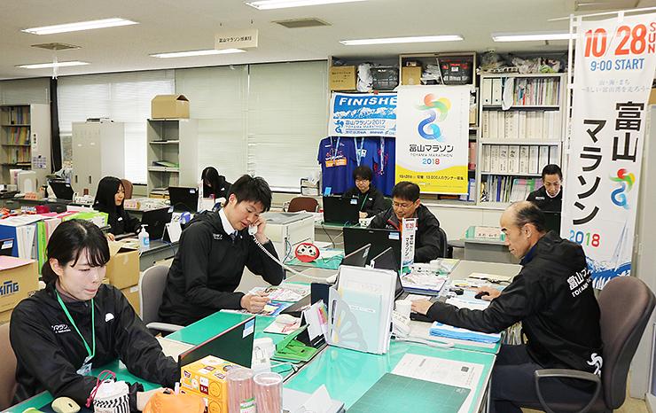 参加先行枠の受け付けが始まり、対応に追われる富山マラソン実行委事務局=県庁