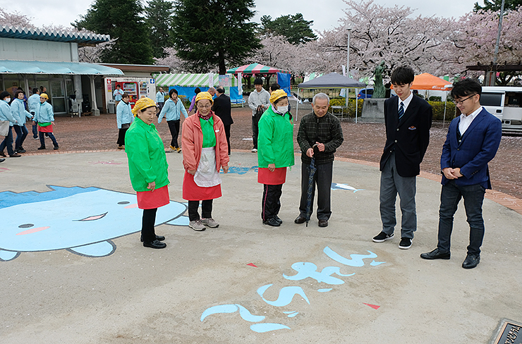 除幕後、アンビグラム作品を見て回る(手前左3人目から)野村さんと飛弾さん、イベントスタッフ