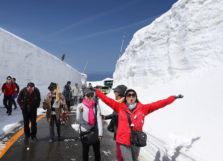 高い雪壁に歓声を上げる外国人観光客=弥陀ケ原