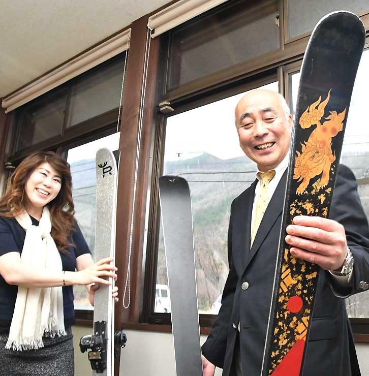 漆塗りのスキー板を手に、製造の打ち合わせをする山崎さん(右)と高木さん