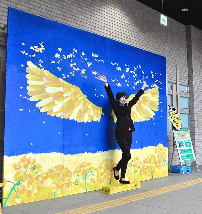 「インスタ映え」を狙ってJR飯山駅構内に設けた撮影スポット。菜の花にちなんだ黄色い天使の羽が生えているような写真が撮れる