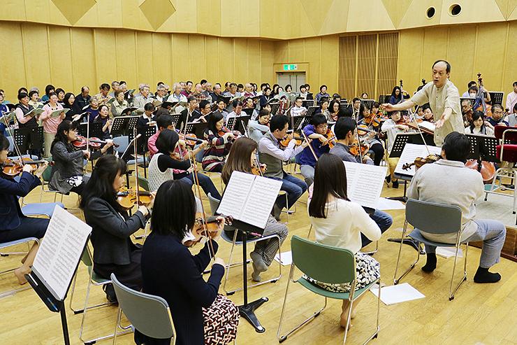 横島さん(右)の指導の下、「ドイツ・レクイエム」の練習をする参加者=富山市民芸術創造センター