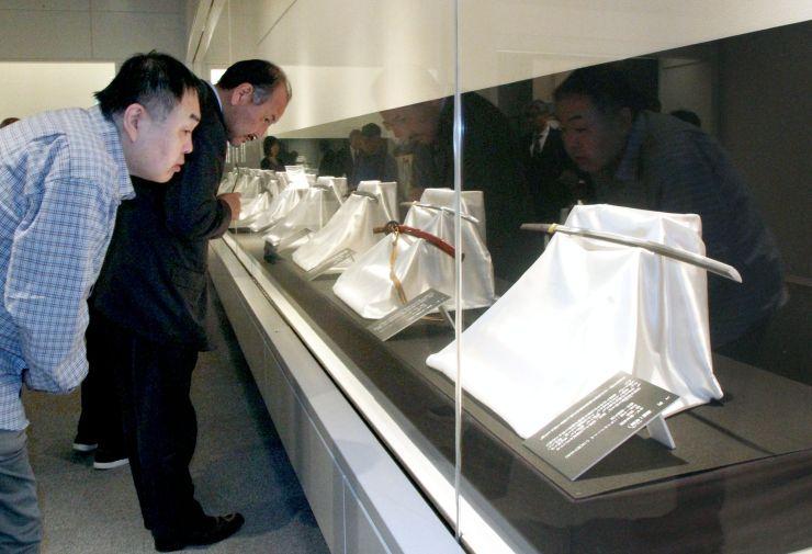 日本刀の美しさに参加者が見入った内覧会=13日、新潟市中央区